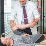 Rafał Mikusek bada staw kolanowy pacjentki